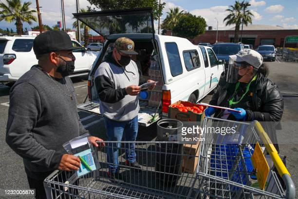 Soledad Enrichment Action community health outreach worker Maria Mejia right, gives information about COVID-19 vaccine to shoppers Pedro Escobar...
