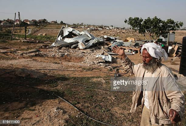 Soleimn a man from the Arab Jahalin Bedouin community reacts next to the rubble of a house in the village of Umm alKheir south of the West Bank city...