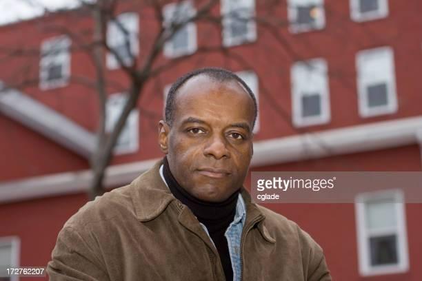 Solemn Black Man In Front of Building