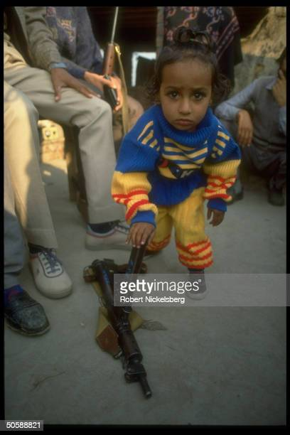 Solemnfaced Sikh child playing w ammo clips belonging to his antimilitant Sikh father ldr of local militia armed by authorities