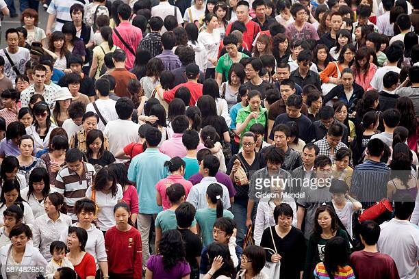 A solid mass of pedestrians cross a busy intersection in the Xidan shopping area during the Mayday holiday break Shopping is one of the most popular...
