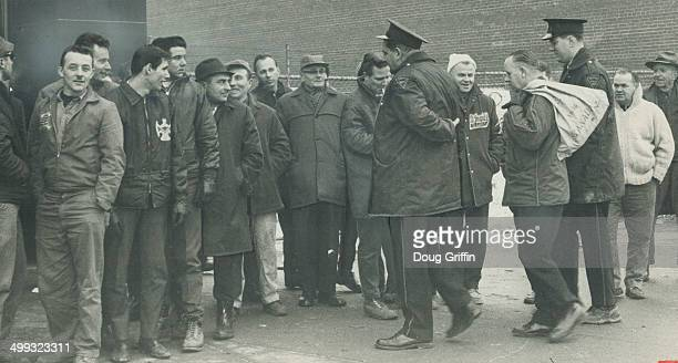 Solid Wall of pickets at the Oshawa Times denies entry to mailing room foreman Frank Baker who arrived at the main entrance flanked by two policemen...