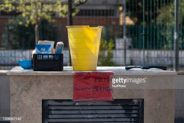 A solidarity collection point is located outside a supermarket in the 'Pigneto' area The sign reads 'Who can leave something who cannot take...