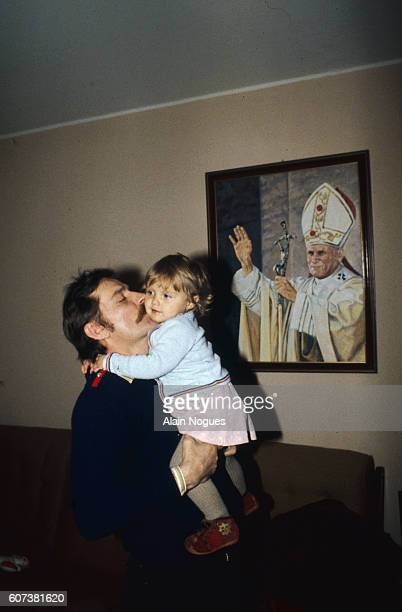 Solidarity union leader Lech Walesa kissing his young daughter next to a portrait of Pope John Paul II