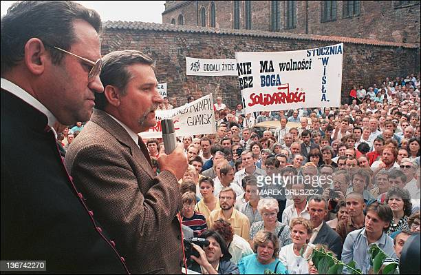 'Solidarnosc' leader Lech Walesa addresses some 10000 striking workers at the Lenin shipyard 14 August 1988 in Gdansk Standing at his right father...