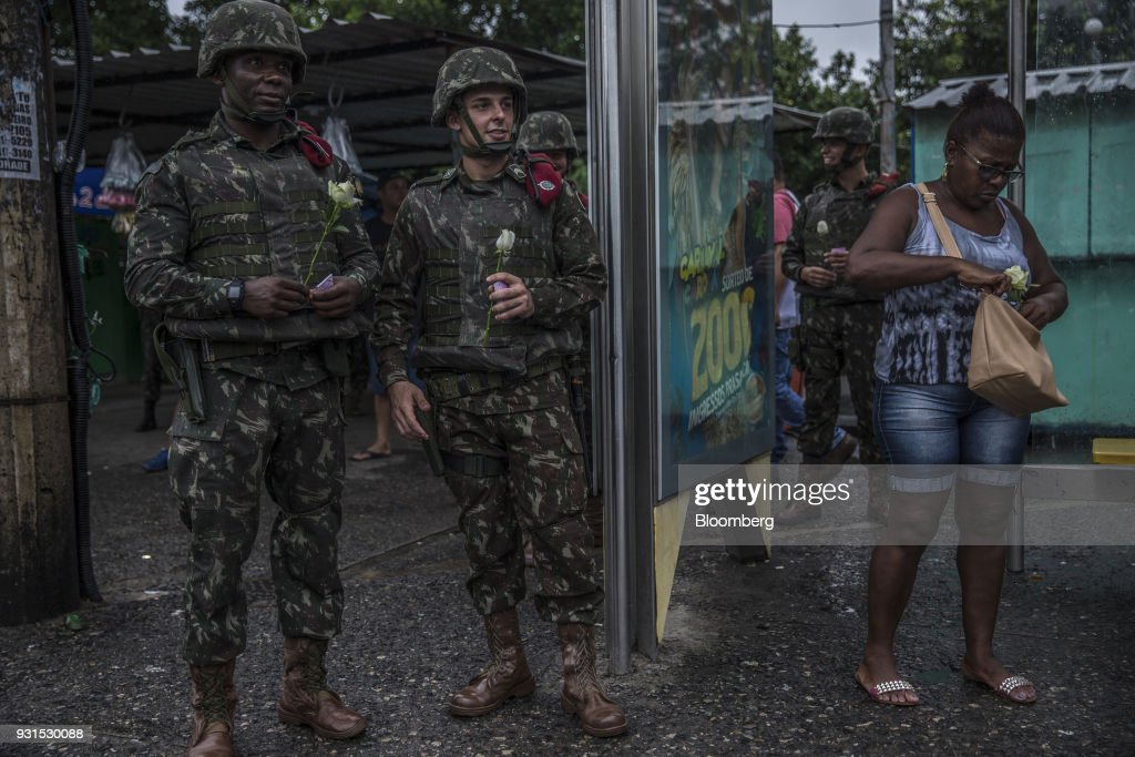 A solider distributes roses to celebrate International Women's Day in the Vila Kennedy neighborhood in Rio de Janeiro, Brazil, on Thursday, March 8, 2018. As public safety remains a top concern for Brazilian voters, President Michel Temer gave the military control of security measures in Rio in an effort increase approval ratings ahead of the country's elections in October. Photographer: Dado Galdieri/Bloomberg via Getty Images