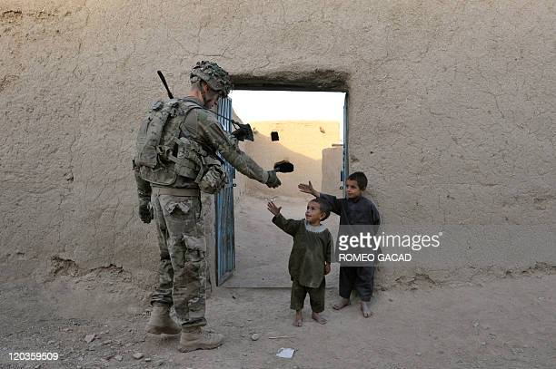 A US solider from the 2nd Platoon Charlie Company 287 3BCT under Afghanistan's International Security Assistance Force greets Afghan children during...