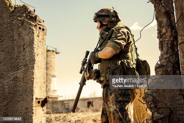 solider holding rifle while standing against sky during sunny day - army soldier stock pictures, royalty-free photos & images