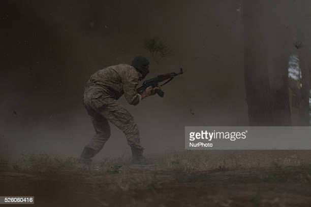 A solider of the Faylaq alRahman brigade shows his skills after an explosion during a military parade on May 30 in the Eastern alGhouta region