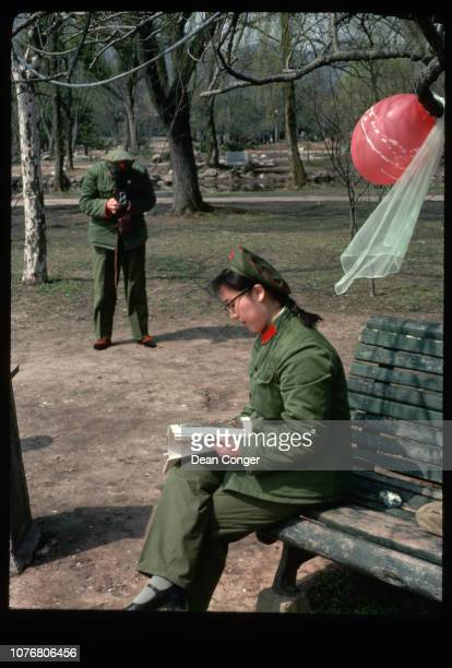 A solider takes a picture of his girlfriend also a soldier sitting on a park bench reading at a park near West Lake Hangzhou Zhejiang Province China
