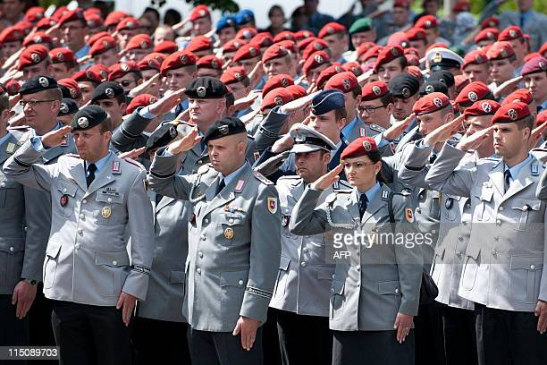 Soliders salute the coffins of three German soldiers after the memorial service for three German soldiers killed in Afghanistan at the Epiphanias...