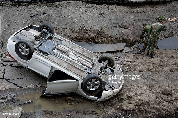 Soliders using electronic devices search through the site of the damaged road after several gas explosions took place in southern Kaohsiung on August...