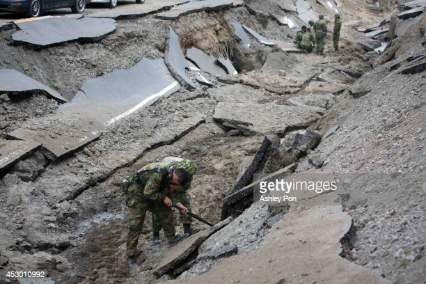 Soliders using electronic devices search through the site on the damaged road after several gas explosions in southern Kaohsiung on August 1, 2014 in...