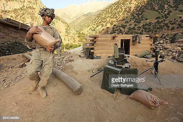 A solidier from Charlie Company US Army 10th Mountain Division carries sandbags at Firebase Lindstrom Barge Matal Nuristan Province