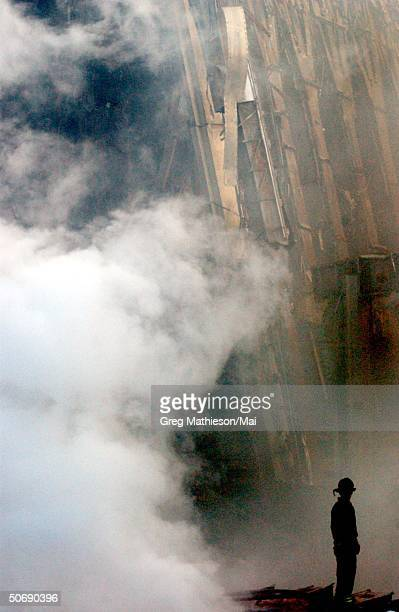 Solitary fire fighter standing amidst rubble and smoke from fires still burning days after the Sept. 11 terrorist attack on the World Trade Center.