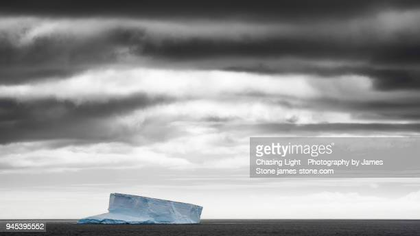 Solitary iceberg under stormy sky