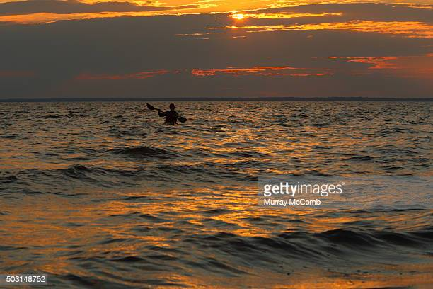Solitary kayaker heading out into an Atlantic Ocean sunset