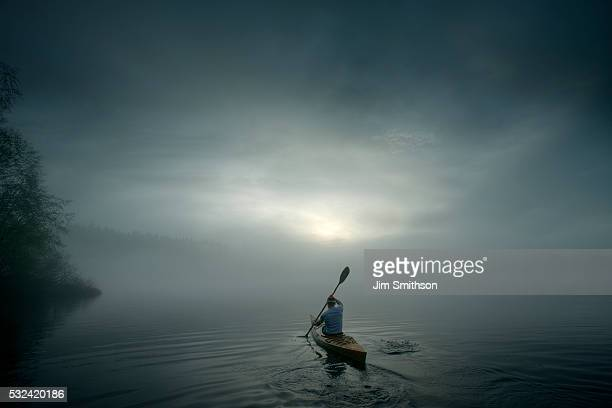 solitary kayaker paddling in calm waters. - bateau à rames photos et images de collection