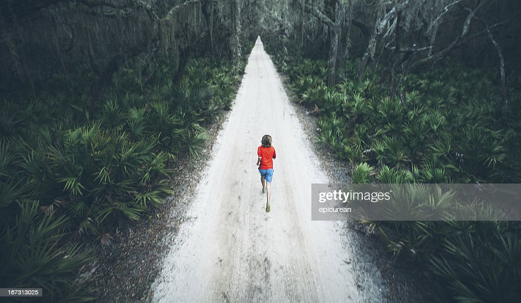 Solitary male runs under trees on road at sunset : Stock Photo