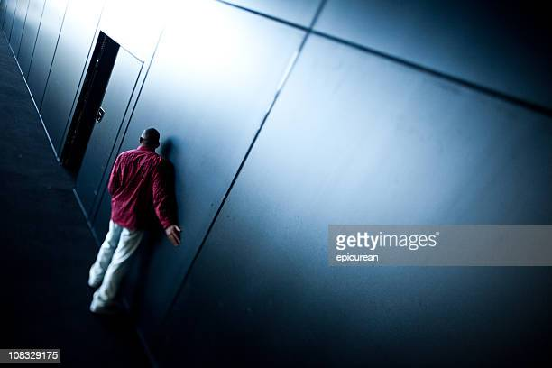 Solitary man creeping towards a dark door