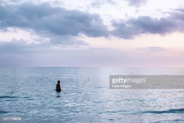 Solitary man in tropical ocean water at Siesta Key Beach in Florida.