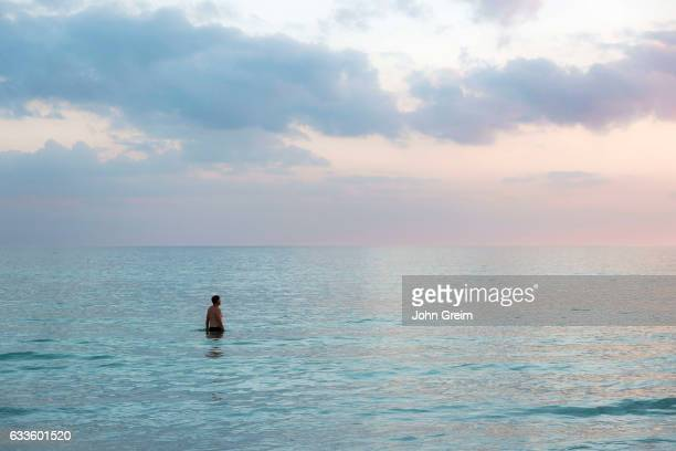 Solitary man in tropical ocean water.