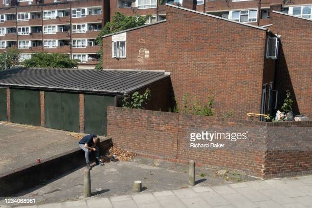 Solitary man is slumped to read his phone during the summer heatwave, next to estate homes in Southwark on Covid 'Freedom Day'. This date is what...