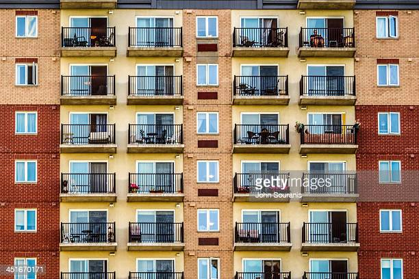 Solitary man sits on his balcony enjoying a late summer afternoon.