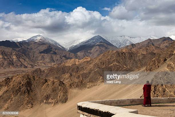Solitary monk by the Ladakh mountains range from Shey gompa near Leh