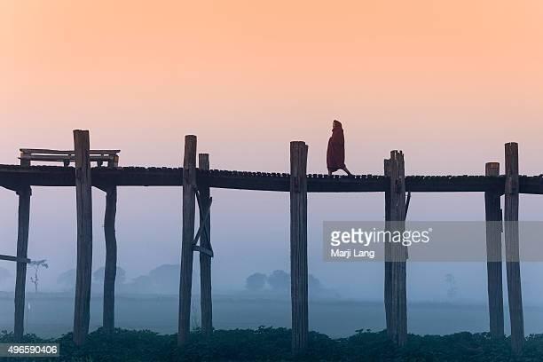 MANDALAY MYANMAR MANDALAY MYANMAR Solitary monk walking on the U Bein bridge in Amarapura by a foggy and misty morning near Mandalay Burma