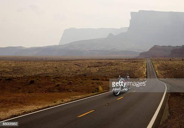 solitary motorcyclist on deserted highway. - fugir da realidade imagens e fotografias de stock