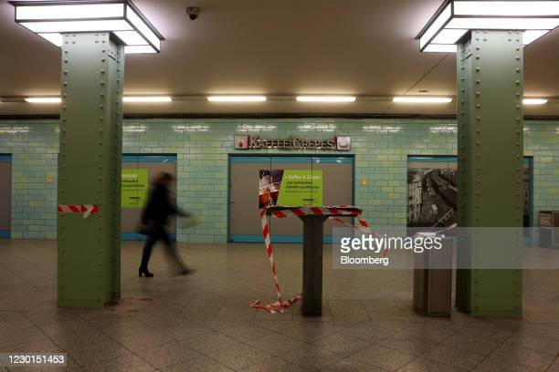 Solitary passenger passes a cordoned off coffee kiosk table at Alexanderpaltz station during morning rush hour in Berlin, Germany, on Wednesday, Dec....