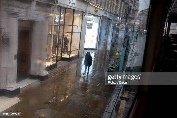 Solitary person walks alone on a wet pavement during seasonal showers on Piccadilly in the capital's West End during the third lockdown of the...