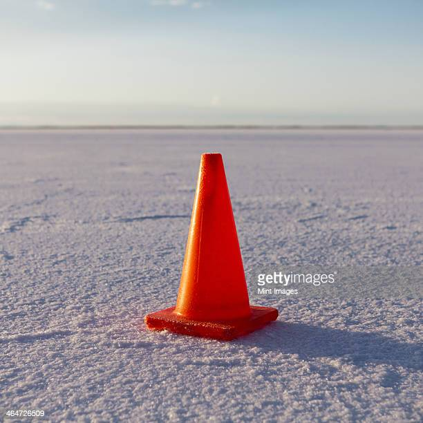 A solitary traffic cone on the white reflective mineral dusted surface of the Bonneville Salt Flats in the early morning light.