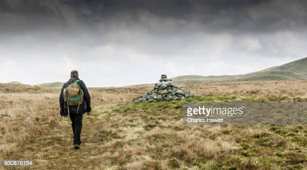 Solitary walker by cairn near Bryn Eithinog, Ceredigion. The Cambrian Way, Wales, UK