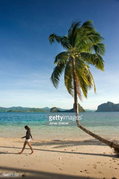 EL NIDO PALAWAN PHILIPPINES A solitary woman strolling on an island in the El Nido archipelago MODEL RELEASED