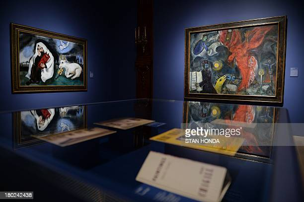 """Solitude, 1933"""" and """"The Fall of the Angel, 1923-33-47"""" both by artist Marc Chagall on display at the Jewish Museum September 10, 2013 in New York in..."""