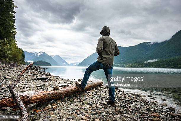 solitude man pensive on the lake side - parka coat stock photos and pictures