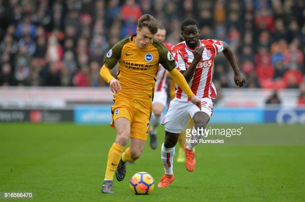Solly March of Brighton and Hove Albion and Kurt Zouma of Stoke City battle for the ball during the Premier League match between Stoke City and...