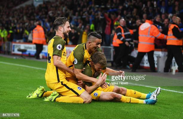 Solly March of Brighton and Hove Albion celebrates as he scores their first goal with team mates Anthony Knockaert and Davy Propper during the...