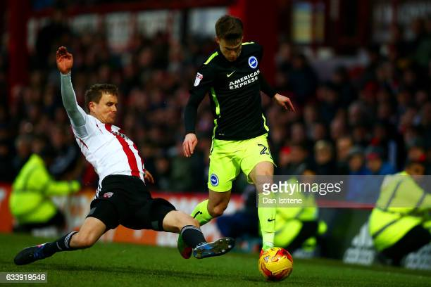 Solly March of Brighton Hove Albion battles for the ball with Andreas Bjelland of Brentford during the Sky Bet Championship match between Brentford...