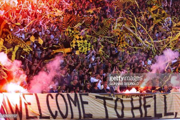 Solna fans display a banner reading 'Welcome To Hell' as they wave flags and cheer in the stands of Rasunda stadium in Stockholm during the Champions...