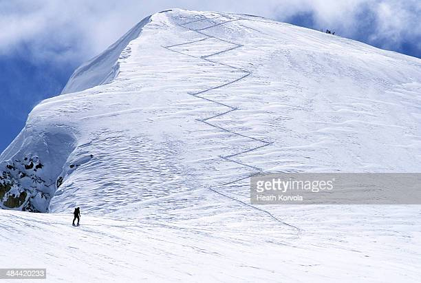 Solo backcountry skier ascending track to peak.