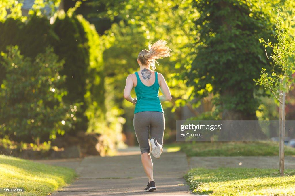 Solo-weibliche Läufer auf einem schönen morgendlichen Jogging : Stock-Foto
