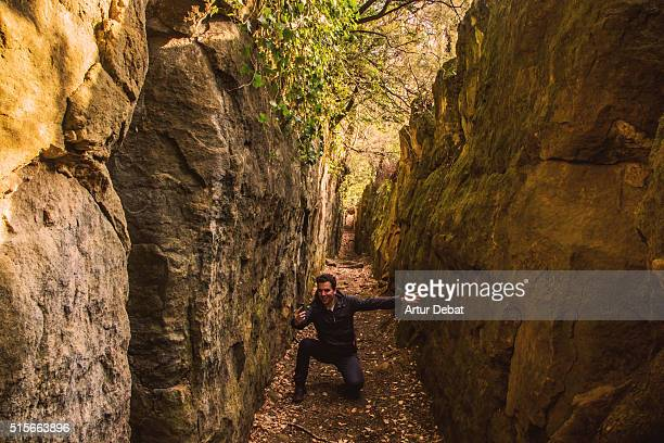 Solo hiker guy taking a selfie from the inside of a wall crack the beautiful narrow path between two crag walls, a wild and hidden place to be discovered in the mountain region of the Garrotxa.