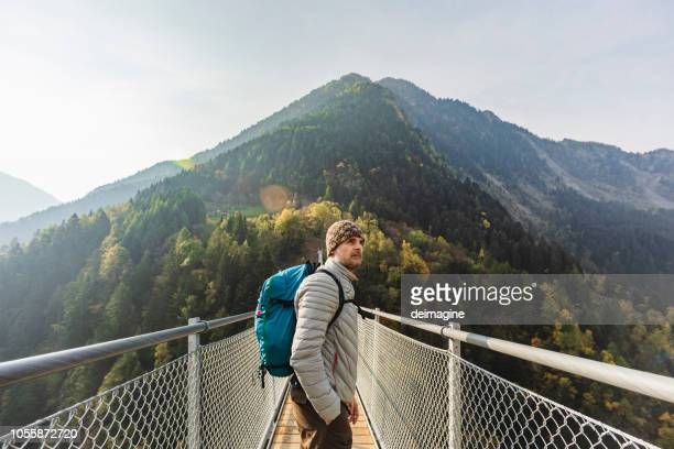 solo hiker looking at view on suspension bridge - pilgrimage stock pictures, royalty-free photos & images