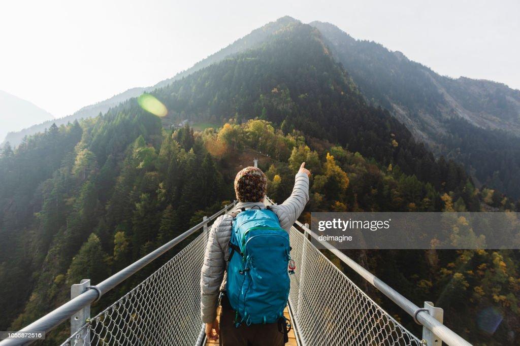 Solo-Wanderer zeigt mit der Hand auf der Hängebrücke : Stock-Foto