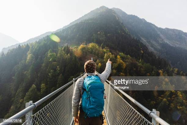 solo hiker pointing with hand on suspension bridge - aspirations stock pictures, royalty-free photos & images