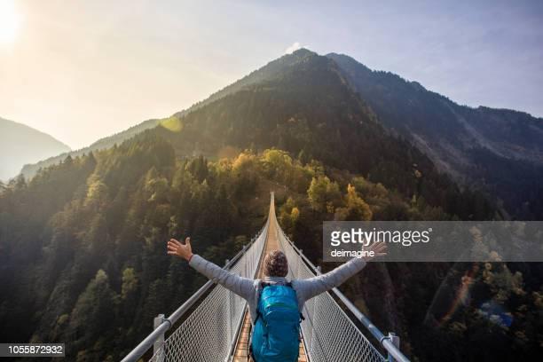 solo-wanderer mit offenen armen auf hängebrücke - hängebrücke stock-fotos und bilder