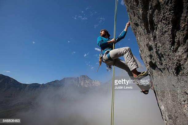Solo Man Ascends Rock Face